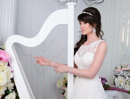 Close up of beautiful woman with harp wearing shiny diamond earrings Stock Photo