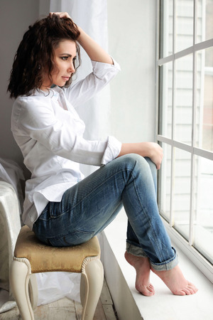 permanent wave: Beauty model woman portrait with curly brown-haired. Casual clothes - white shirt and blue jeans in the studio