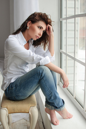perming: Beauty model woman portrait with curly brown-haired. Casual clothes - white shirt and blue jeans in the studio