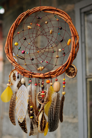 dream vision: Handmade brown dream catcher at wall in background