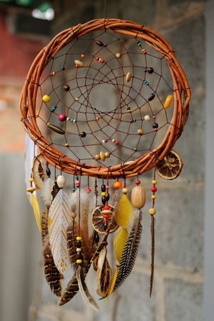 Handmade brown dream catcher at wall in background