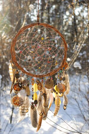 colorfull: Handmade colorfull dream catcher in the snowy forest. Tribal elements, owl feathers
