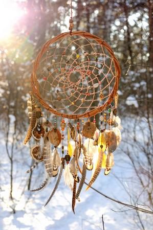 Handmade colorfull łapacz snów w zaśnieżonym lesie. Elementy plemienne, pióra sowy
