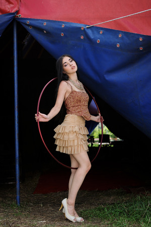 behind the scenes: Beautiful girl with hula hoop in designer dress is behind the scenes of the circus. Circus tent