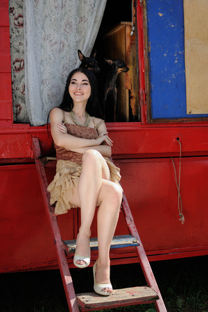 behind the scenes: Fashionable girl guarded by two toy terrier dogs. Behind the scenes of the circus. On background of red-blue circus trailer Stock Photo