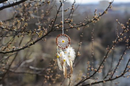 dream lake: Handmade native american dream catcher on background of rocks and lake. Tribal elements, feathers