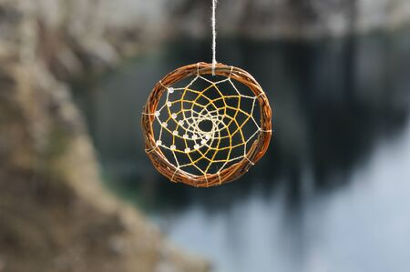 dream lake: Handmade dream catcher on background of rocks and lake. Tribal elements