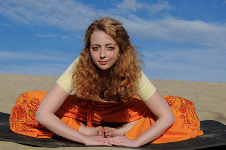bound woman: Young slim redhead woman sitting in purna titli yoga pose on the beach. bound angle, butterfly pose on the background of the sand and sky