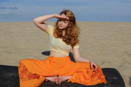 donna farfalla: Young slim redhead woman sitting in purna titli yoga pose on the beach. butterfly pose. on the background of the sand and sky Archivio Fotografico