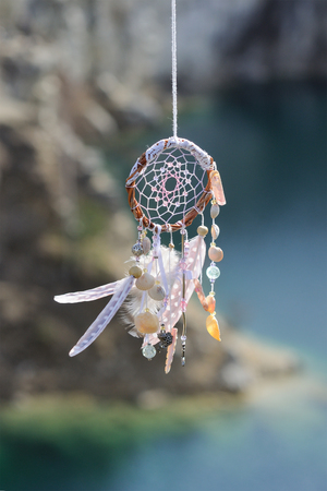 dream lake: Handmade pink native american dream catcher on background of rocks and lake. Tribal elements, feathers, shells, lace