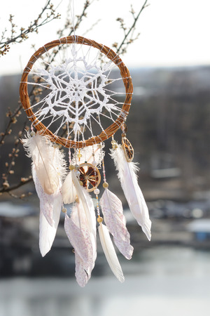 dream lake: Handmade pink native american dream catcher on background of rocks and lake. Tribal elements, feathers, lace, crochet snowflake doily