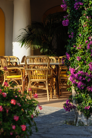 Tables and wicker chairs in the outdoor restaurant in Italy Stock Photo