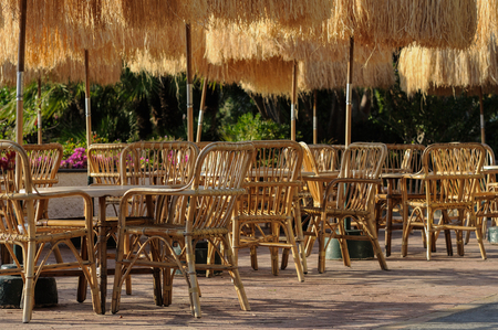 Tables and wicker chairs with straw sunshades in the outdoor restaurant in Italy