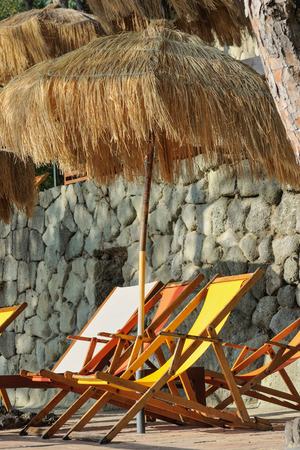 Sunbeds and straw sunshades in Italy
