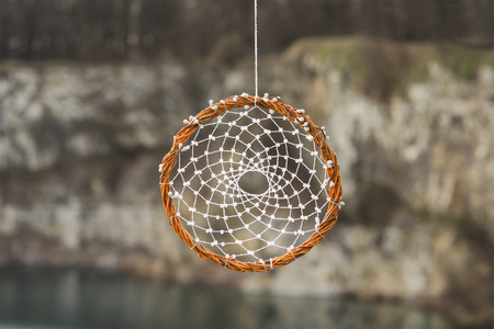 Handmade dream catcher on background of rocks and lake. Tribal elements, feathers