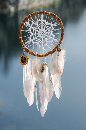 Handmade pink dream catcher with white doily on background of rocks and lake. Tribal elements, feathers, lace, crochet snowflake