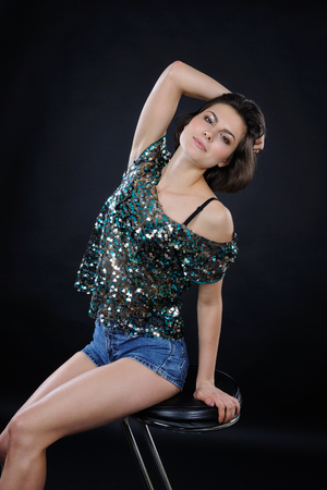 Athletic girl in shiny blouse and denim shorts in the studio on dark background Фото со стока