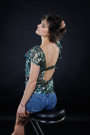 Athletic girl from back in shiny blouse and denim shorts in the studio on dark background Фото со стока