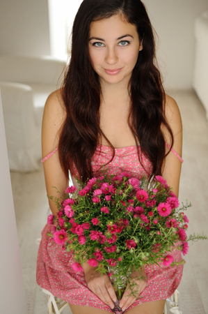 Pretty girl sitting with a bouquet of flowers in pink floral dress and white corset Фото со стока