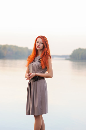 Outdoors portrait of beautiful confident young woman with long red hair in casual dress, colorful autumn, river sunset
