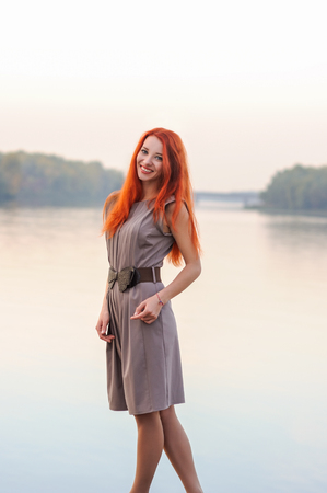 Outdoors portrait of beautiful smiling young woman with long red hair in casual dress, colorful autumn, river sunset Фото со стока