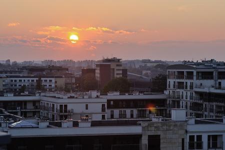 Krakow city architecture with sunset across horizon. Urban background, sunny haze, dusk time Фото со стока