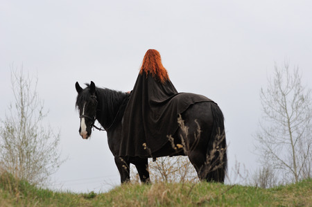 Brave woman with red hair in black cloak on a purebred friesian horse, girl from the back