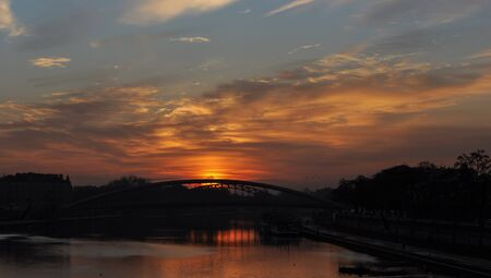 Background of river and bridge at sunset time, sky light at dawn and twilight. Autumn trees   Фото со стока