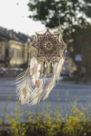 Handmade mandala Gods Eye dream catcher with white peacock feathers and amethyst crystals on city background in sunset time