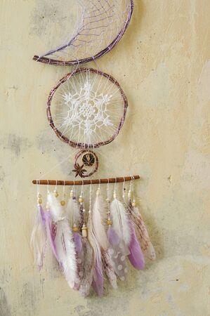Closeup details modern dreamcatcher with gemstones, crochet mandala doily snowflake, painted feathers, cinnamon stick, star anise, dried lemon