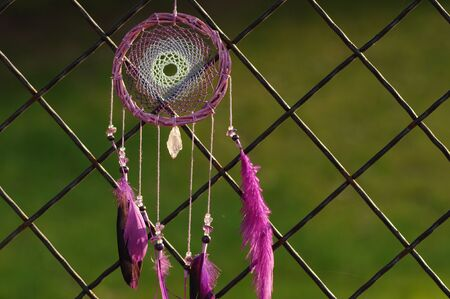 Closeup modern dreamcatcher with purple feathers outdoors