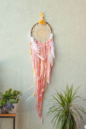 Pink dreamcatcher with white feathers on gray background