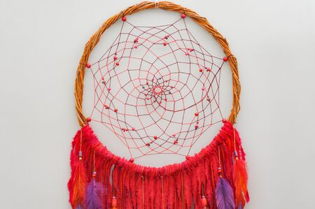 Closeup details modern dreamcatcher with painted colorful feathers on gray background