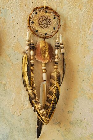 Closeup details modern dreamcatcher with painted golden feathers on brown old wall Standard-Bild