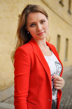 Beautiful smiling young girl with freckles in red blazer streetstyle look