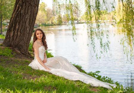 Fantasy portrait of elegant bride in white wedding dress sitting near river