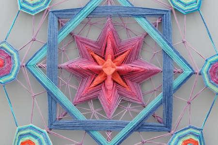Woven colourful handcrafted yarn mandala on gray background 版權商用圖片