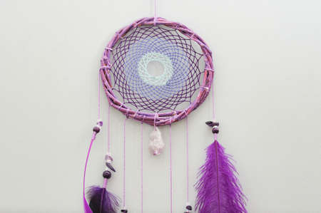 Closeup details modern dreamcatcher with purple ostrich feathers on gray background