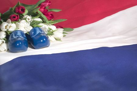 A dutch flag, red & white tulips and blue wooden shoes. photo