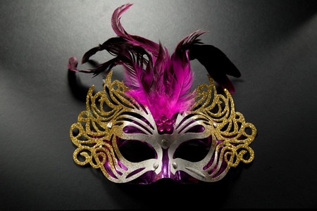 Carnival mask with pink feather on dark backgroud photo