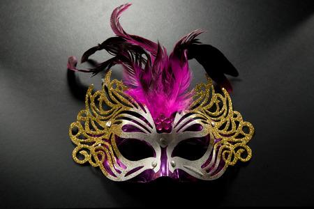 mascara de carnaval: Máscara de carnaval con plumas de color rosa sobre fondo de color oscuro