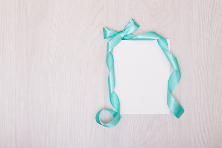 note booklet: Creative mock up with ablank piece of paper. blue ribbon and bow. Empty sheet of paper.