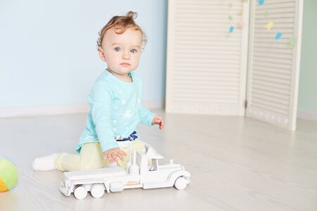 child plays with a car in the studio