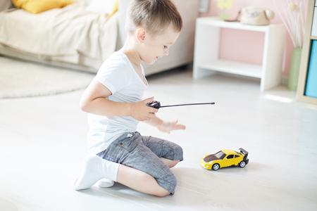 un garçon jouant avec une télécommande de voiture
