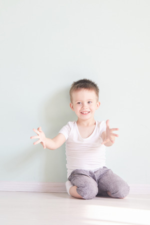Happy cute child reaching out his palms and catching something. Archivio Fotografico