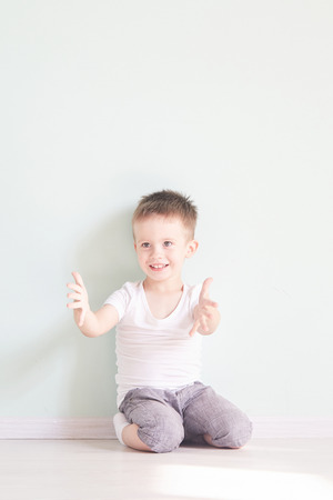 Happy cute child reaching out his palms and catching something. Imagens