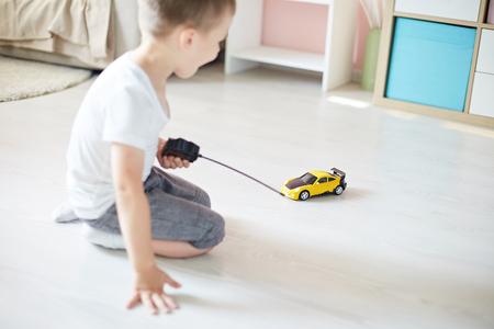 Un garçon jouant avec une télécommande de voiture Banque d'images - 92233622
