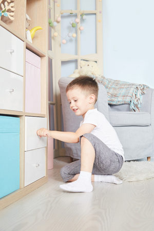 Boy in the hands sat on the floor near the wardrobe