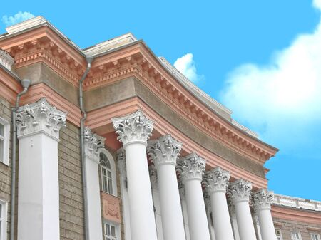 Elegant architectural creation in antique style on a background of the blue sky