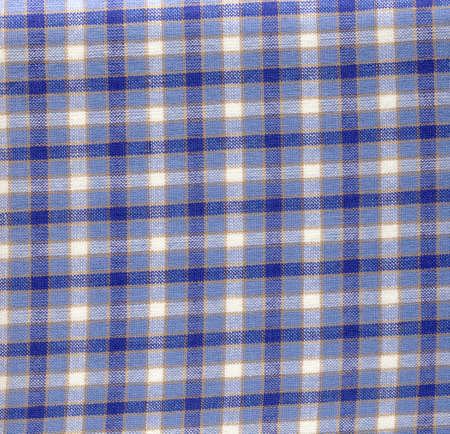 Fragment of a cotton white fabric with a dark blue checkered pattern. photo